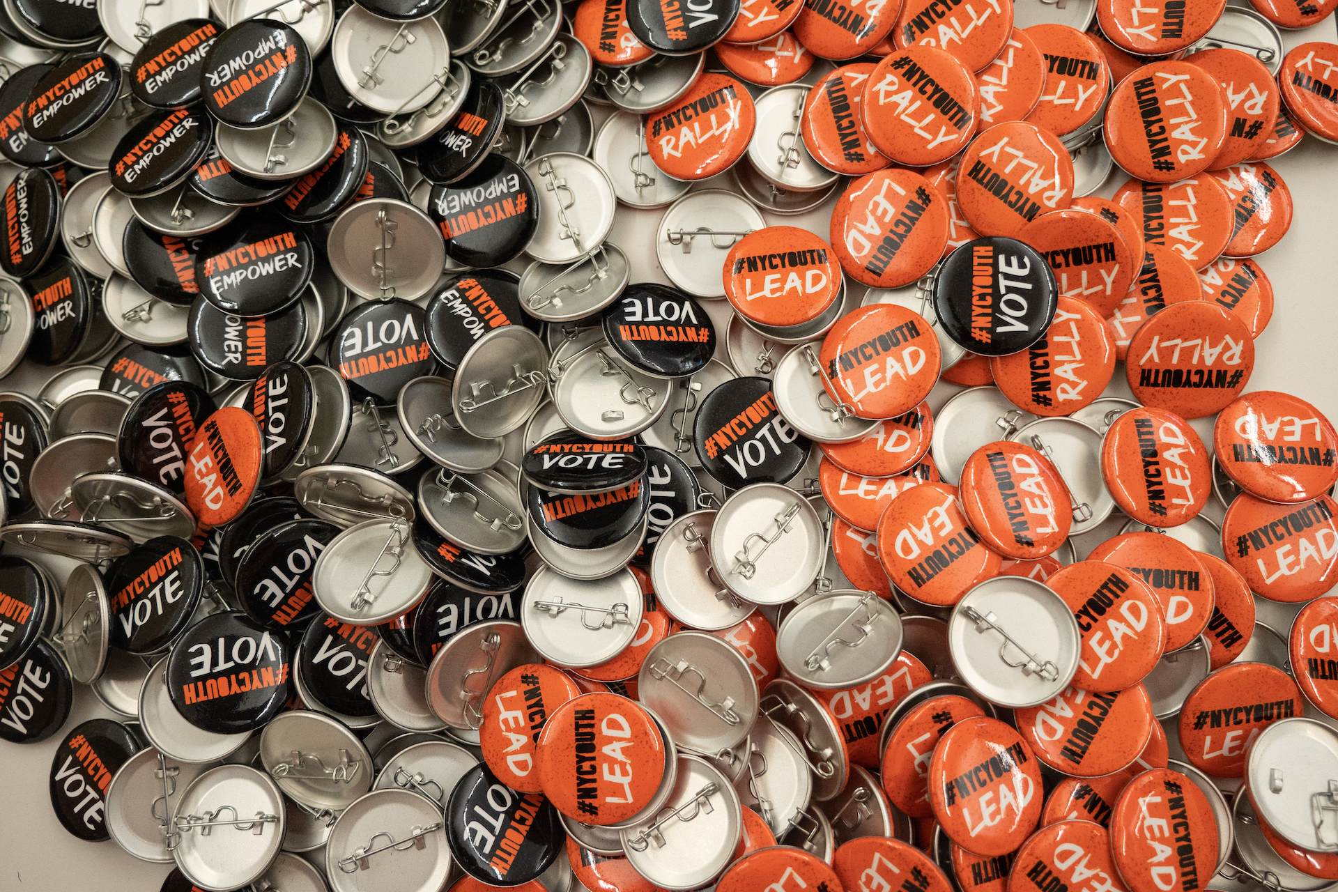 Orange and black round one inch pinback buttons designed individually with the phrases #nycyouth rally, #nycyouth lead, #nycyouth empower, and #nycyouth vote for the Democracy Corps Day of Action event.