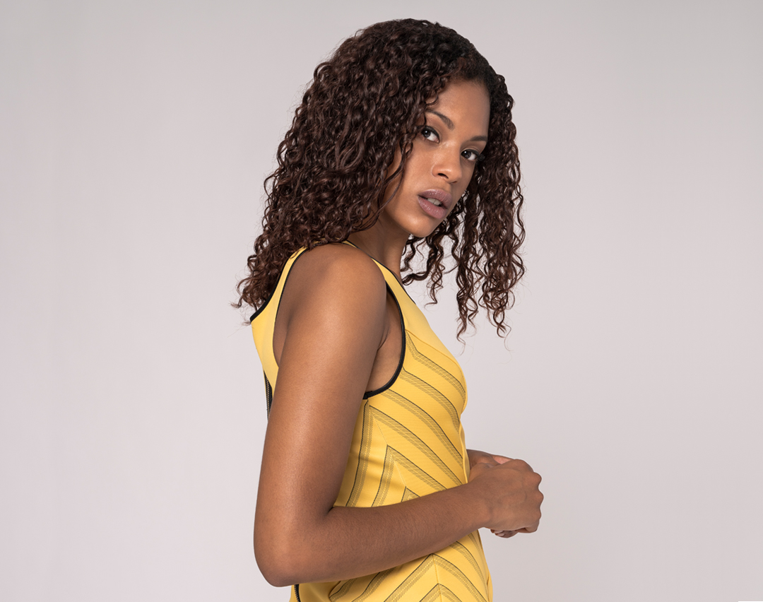 front view of a black model wearing a yellow sheath dress