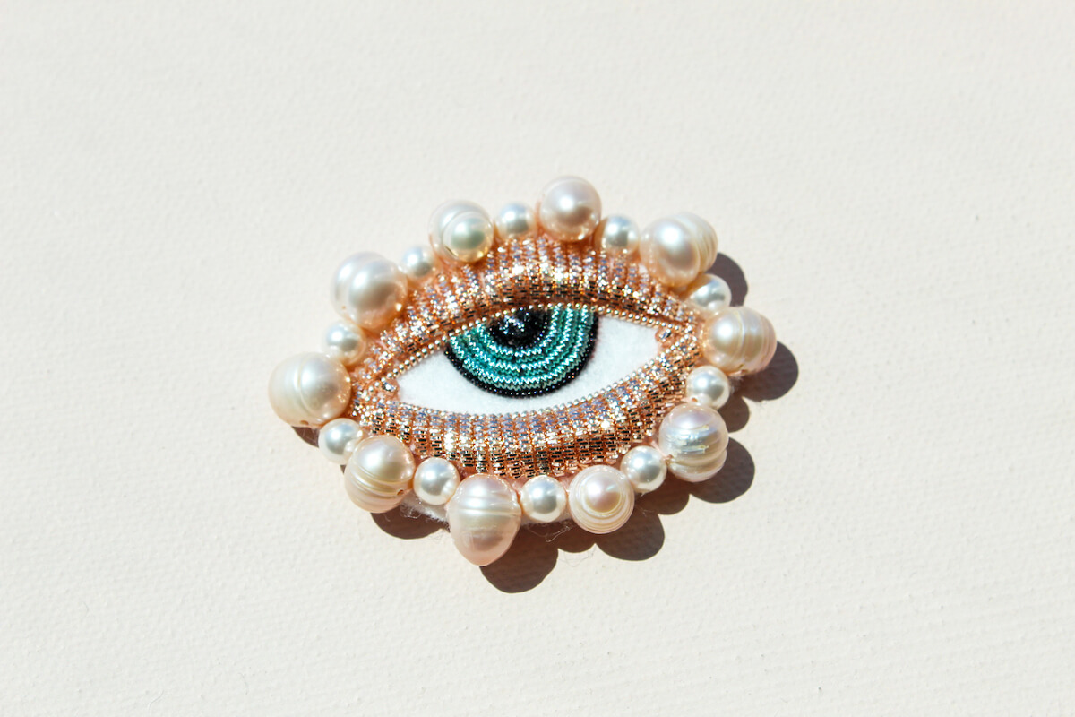 Brooch made from rose gold beads in the shape of an eye with bright blue iris