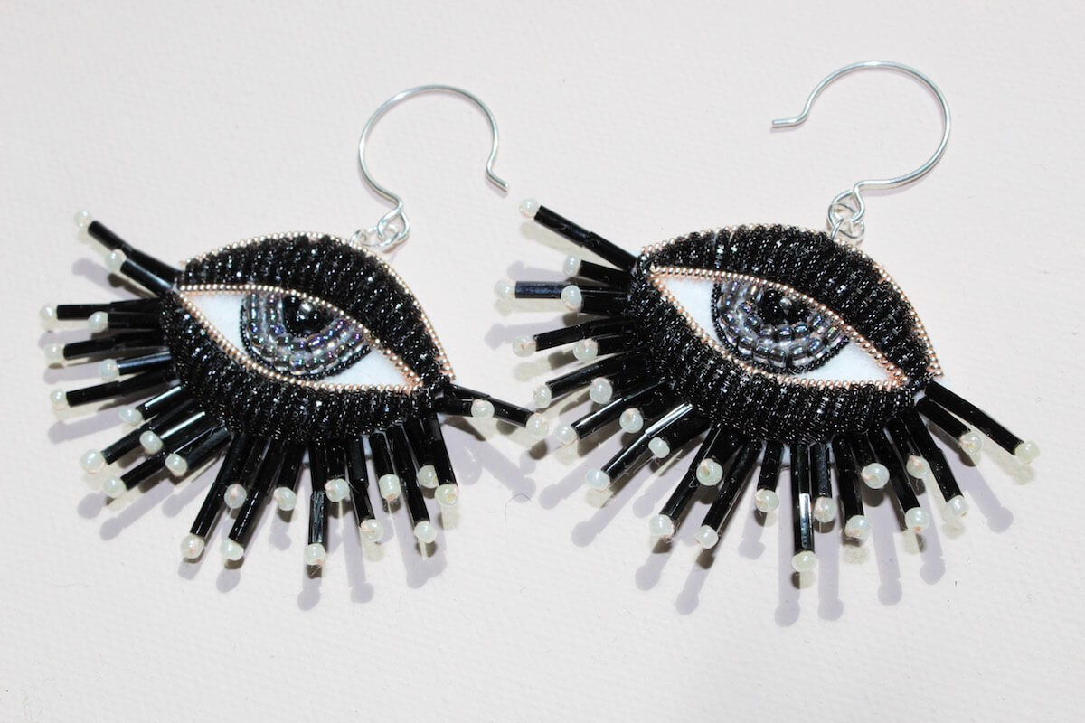Earrings made from black beads in the shape of eyes with blue irises