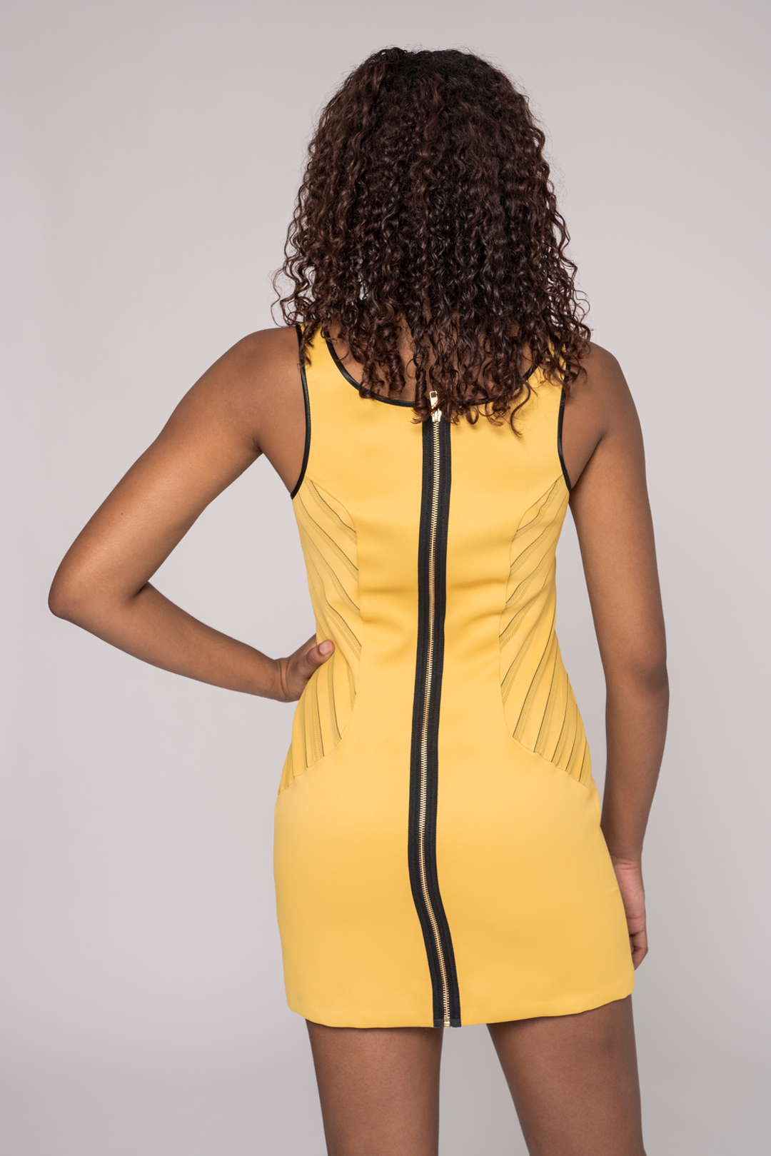 back view of a black model wearing a yellow sheath dress