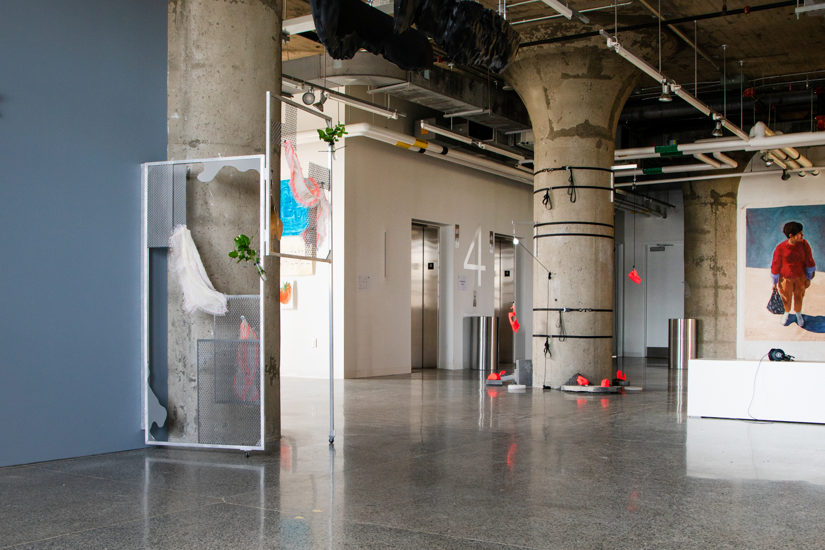 From left to right, on a structural grey column, a sculptural assemblage by Dreifelds using an alumninum door frame, wire mesh scraps, bandages, and plants. On anoteher column to its right, another assemblage by the same artist made of black strapts, neon sculptures of body parts, and pulleys. A mural-like painting of a figure in red sweater by Olou. The white bench with black headphones for an audio work by Workman reappears.