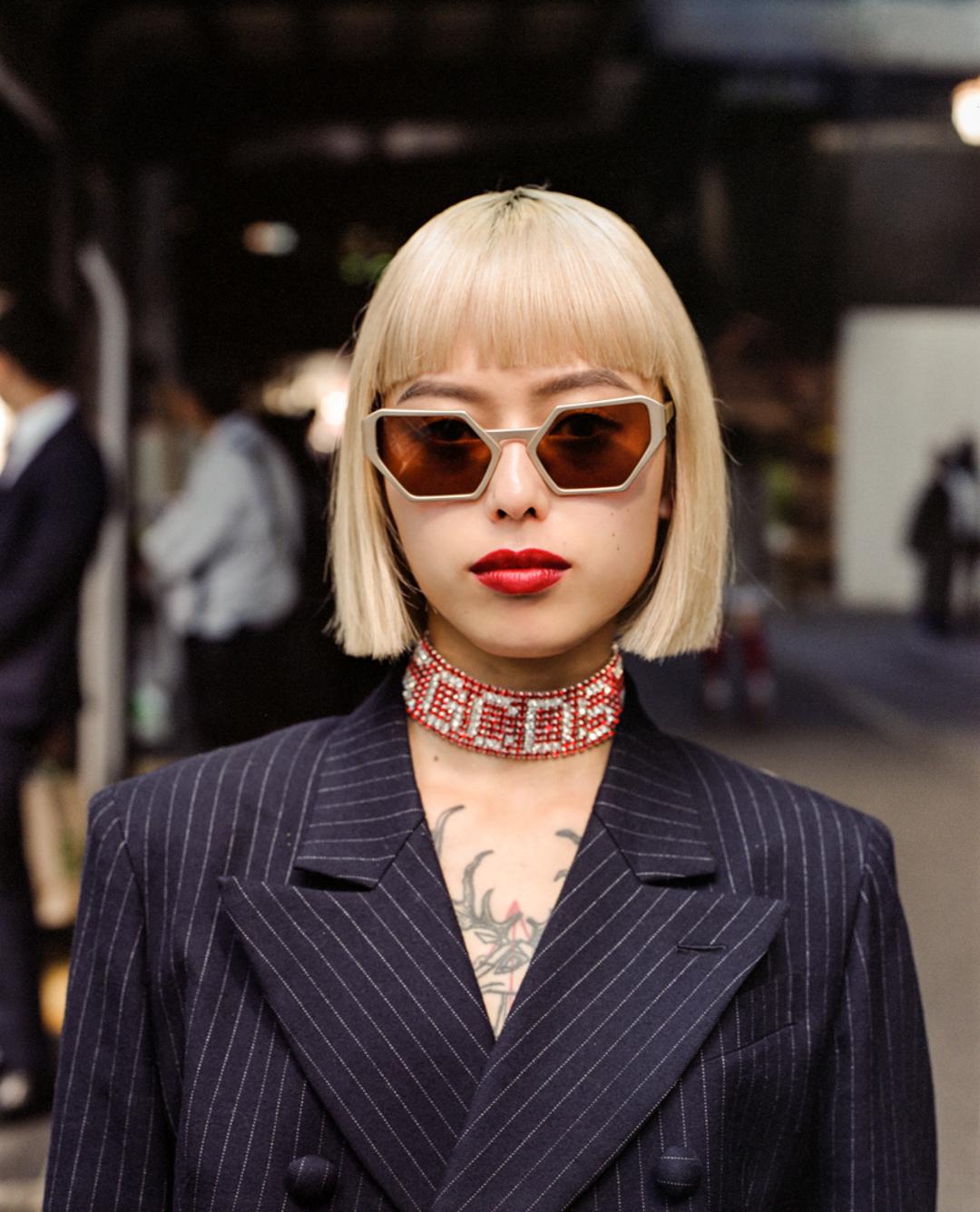 Erika wearing a double-breasted jacket and geometrical sunglasses in Shibuya