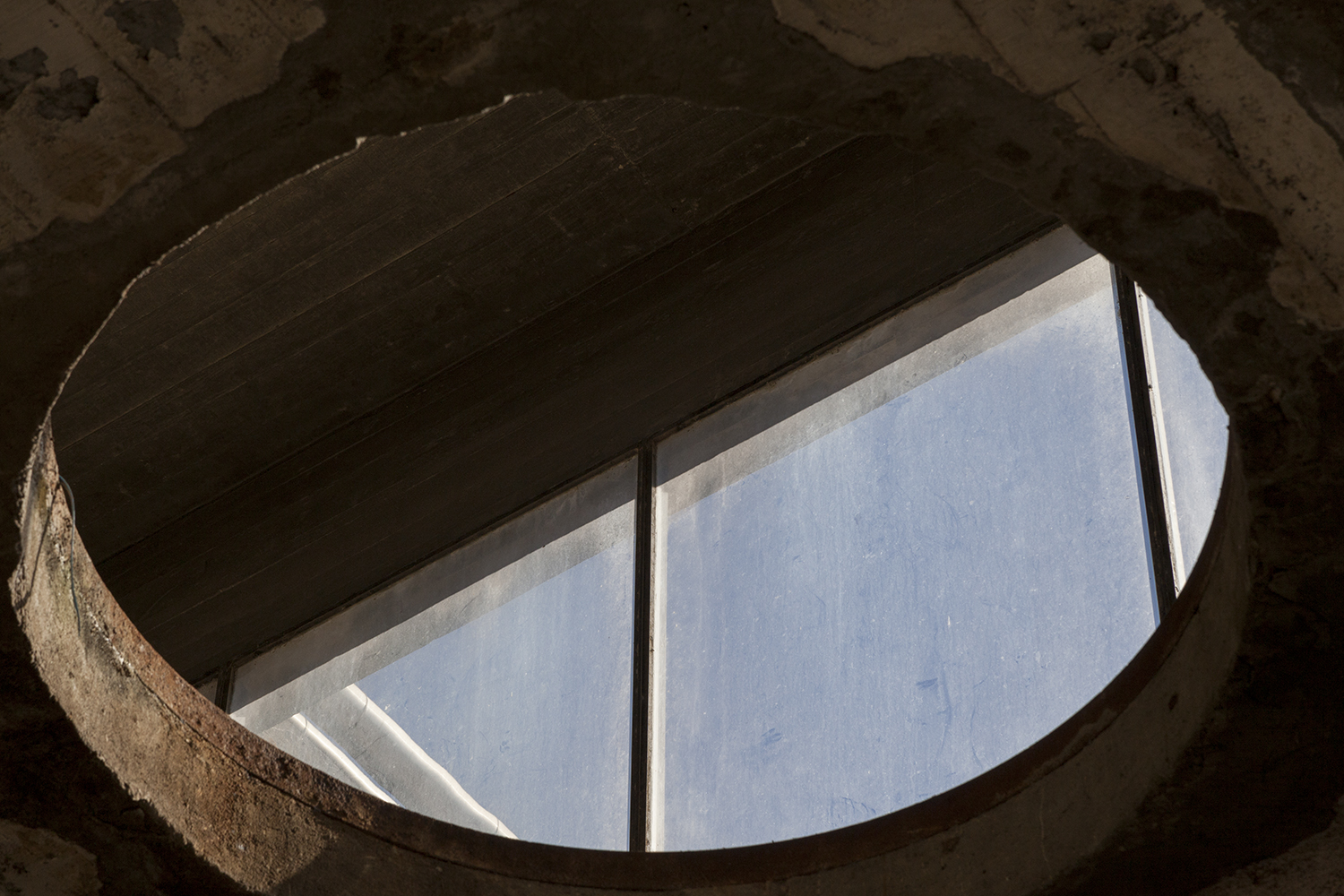 carina martins, vertical ascent - circular window in the roof in an abandoned factory