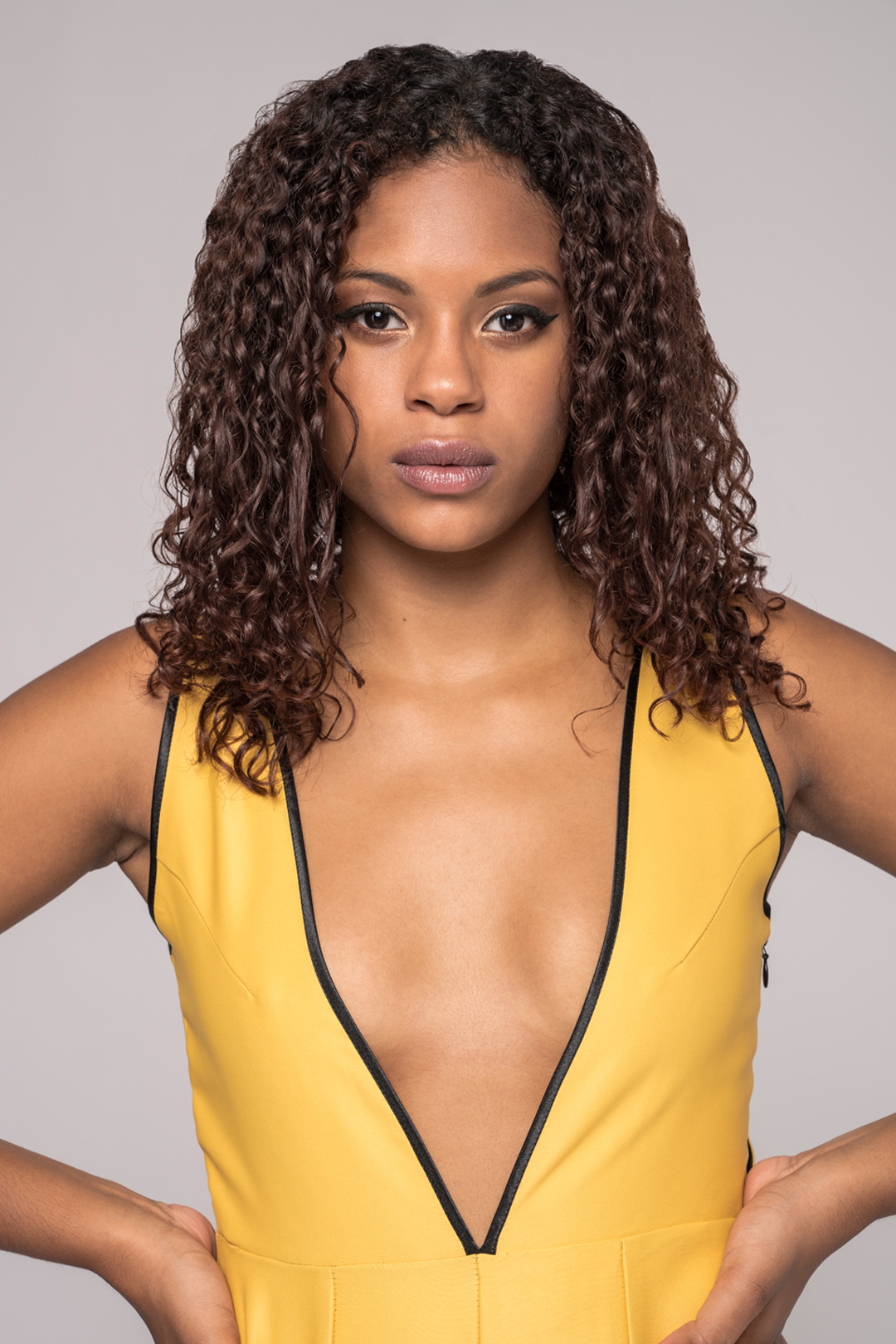 close view of a black model wearing a yellow v-neck jumpsuit