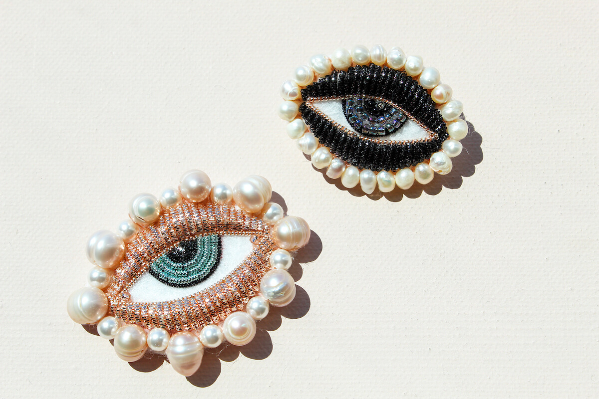 Two brooches one with rose gold beads and one with black beads with pearls around the border