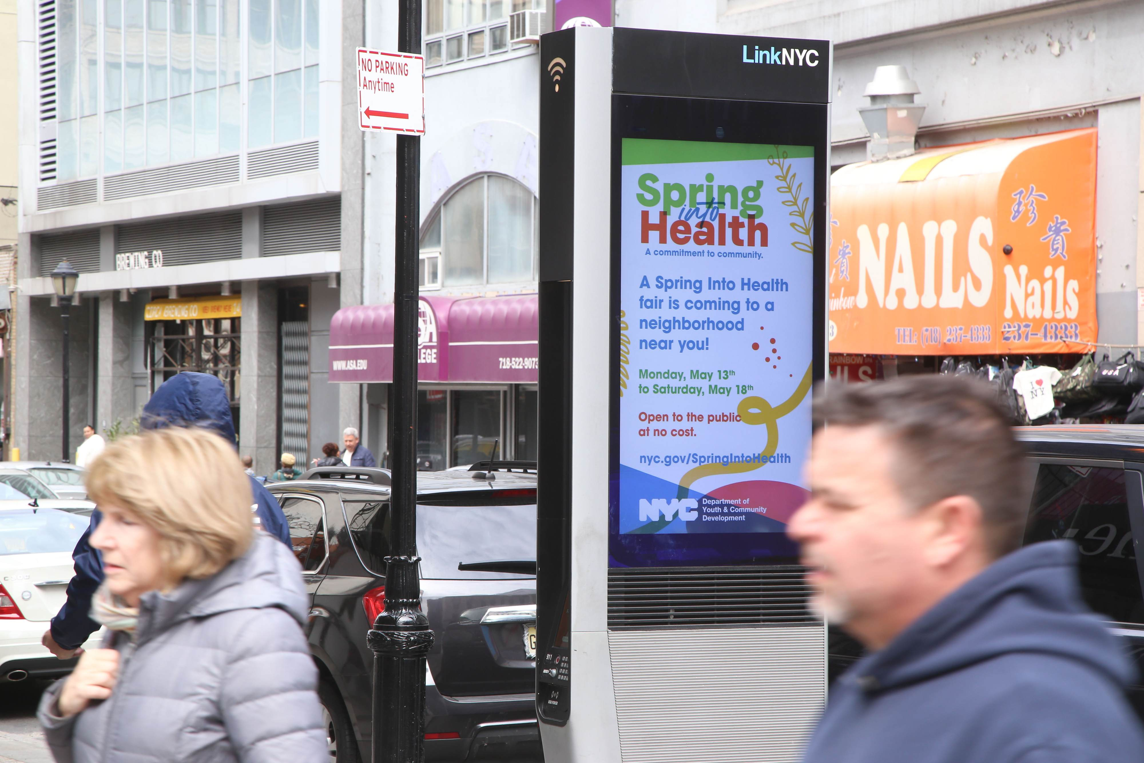 A LinkNYC kiosk displaying the DYCD Spring Into Health Fair advertisement.