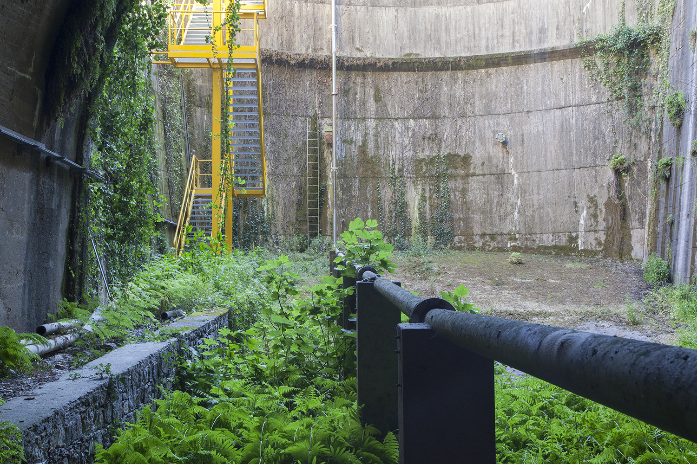 tunel de barragem com conduta de agua e escadas amarelas e plantas silvestres