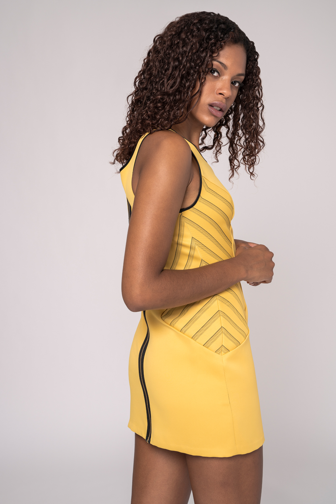 side view of a black model wearing a yellow sheath dress