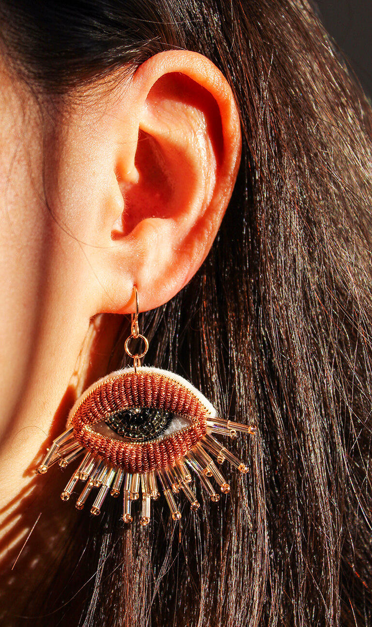 woman wearing a beaded earring in the shape of an eye