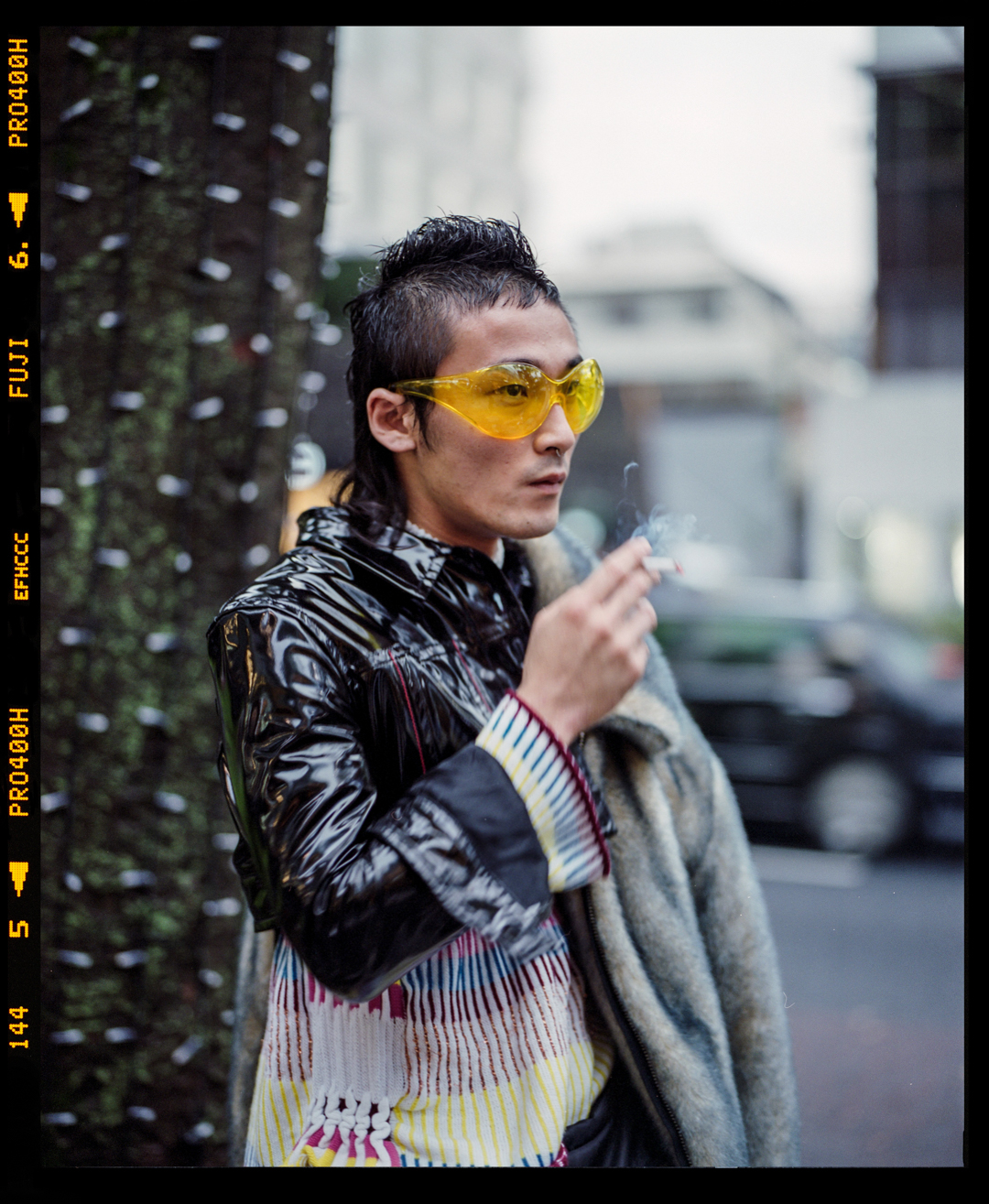 A young Japanese stylist with yellow-tinted glasses and PVC jacket in Omotesando