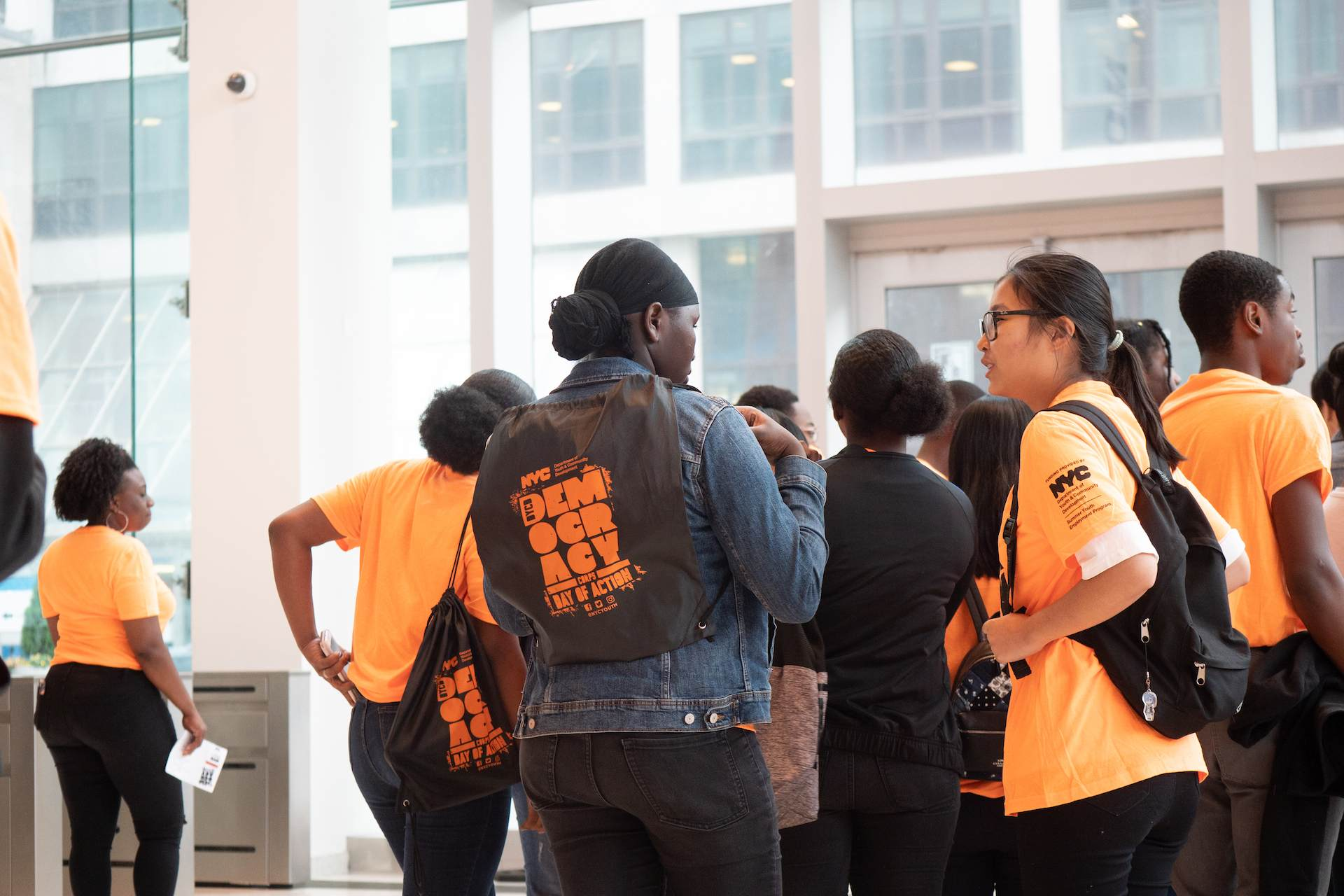 A group of youth participants socializing while wearing black and orange branded Democracy Corps apparel.
