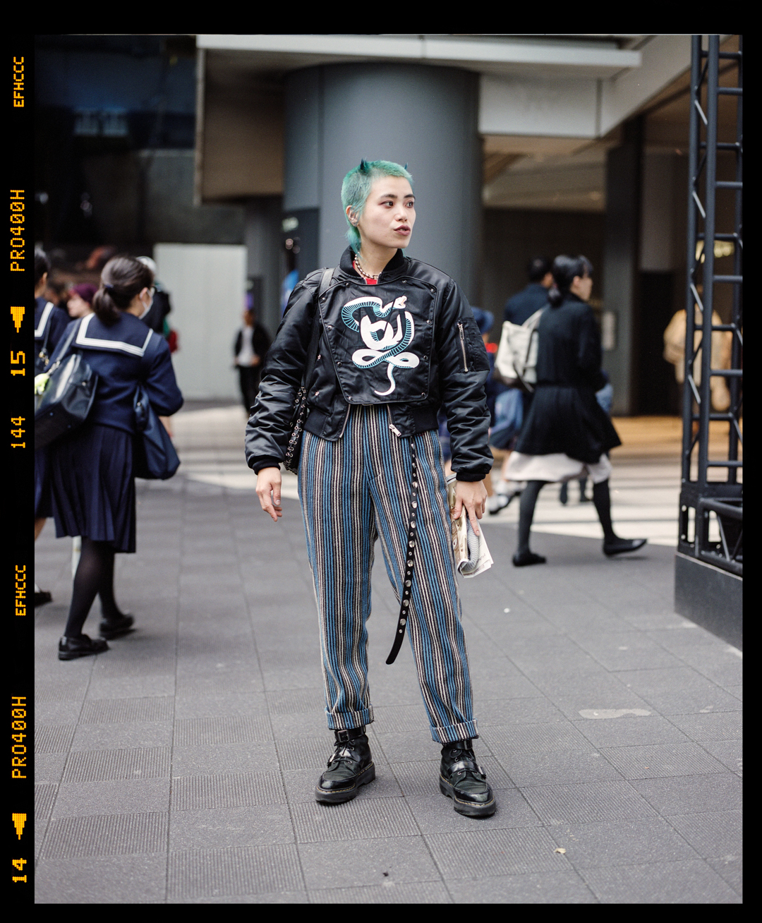 Erino wearing a DIY leather jacket and striped pants in Shibuya