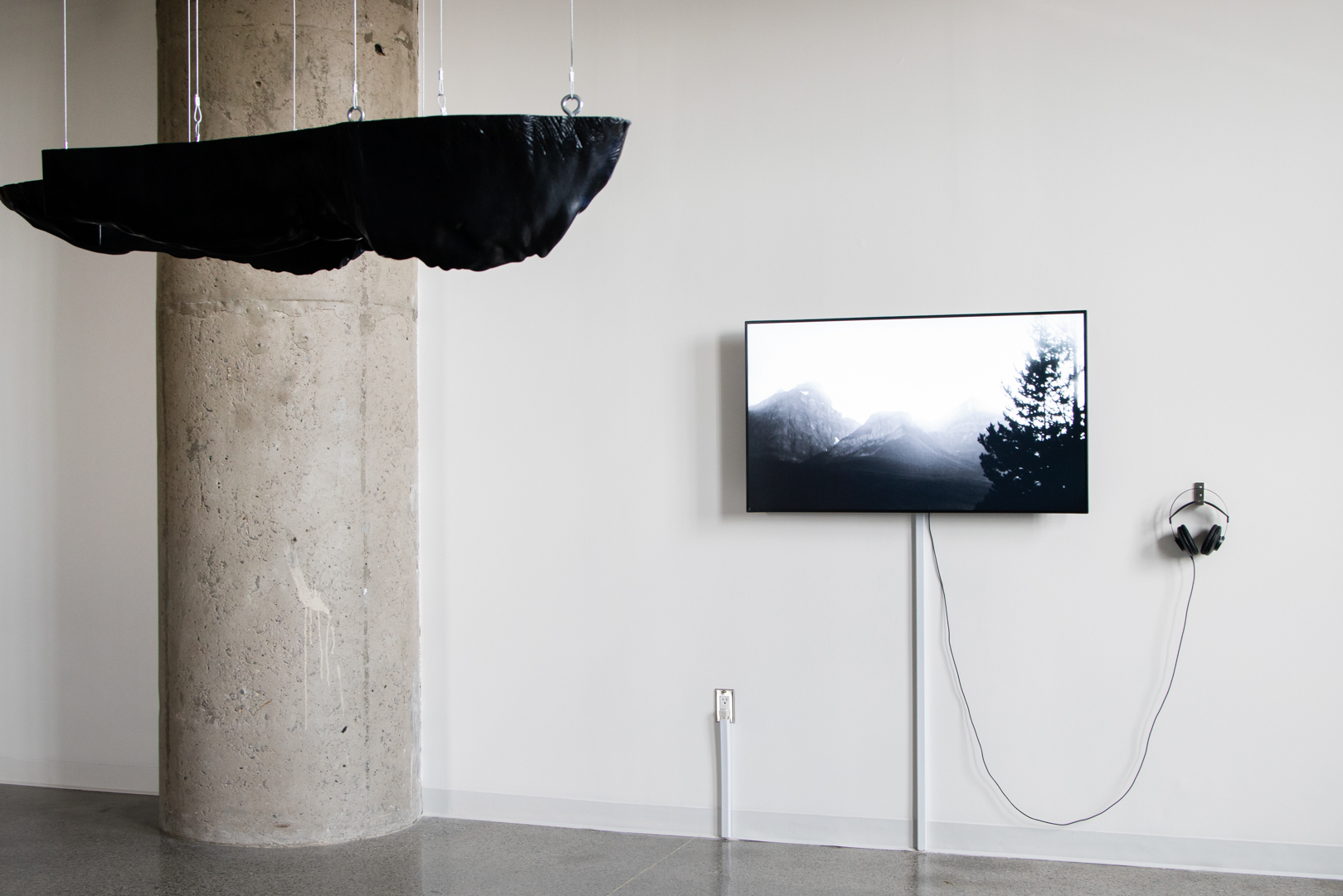 Closer view of the black three-dimensional sculpture by Polymetis. Its top surface is straight and smooth, but in contrast the rest of the sculpture is organic and reminiscent of landscape. Behind it, the black-and-white video of work by Kolcze depicts mountains and trees.