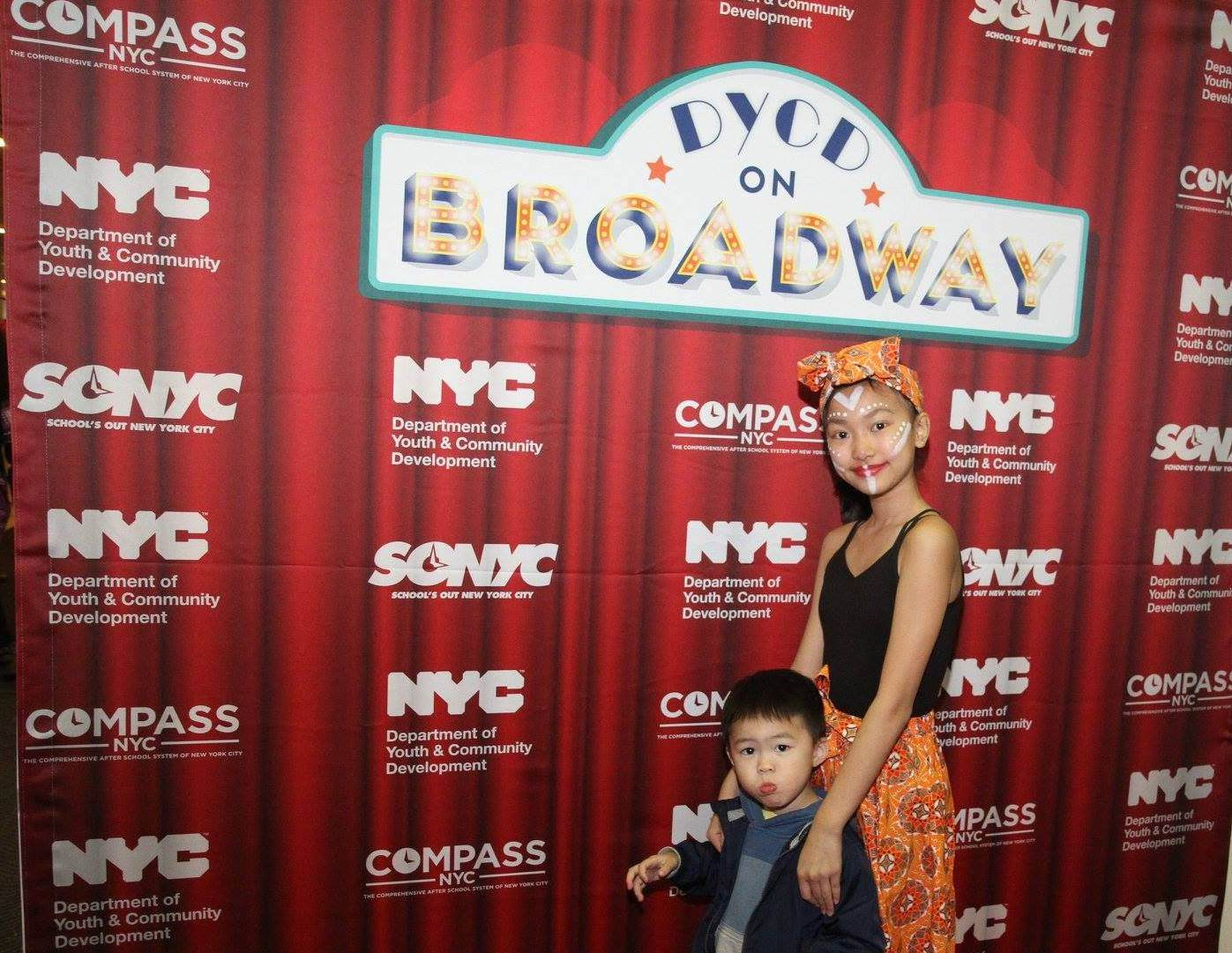 A young girl and small child pose in front of a red step and repeat designed to imitate red theatre stage curtains. The DYCD on Broadway logo is positioned high and centered on the step and repeat with the DYCD, SONYC, and COMPASS logos repeating in a pattern.