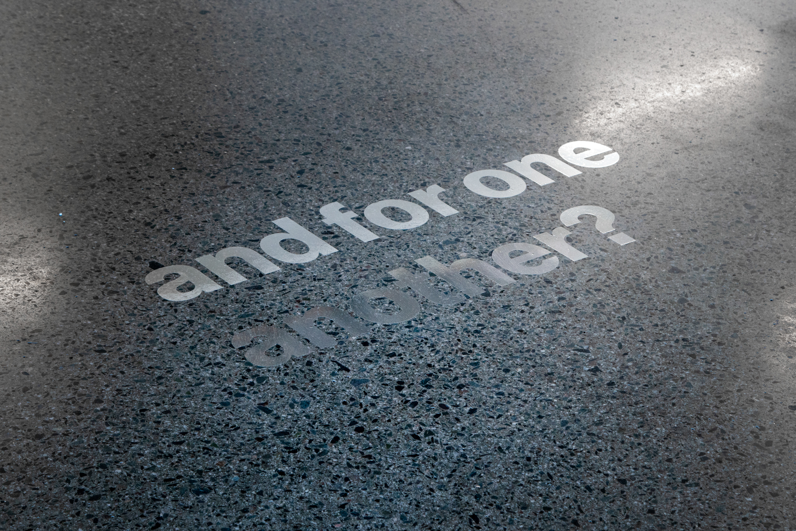 On the grey floor, a silvery vinyl text reads, quote, and for one another?, end quote.