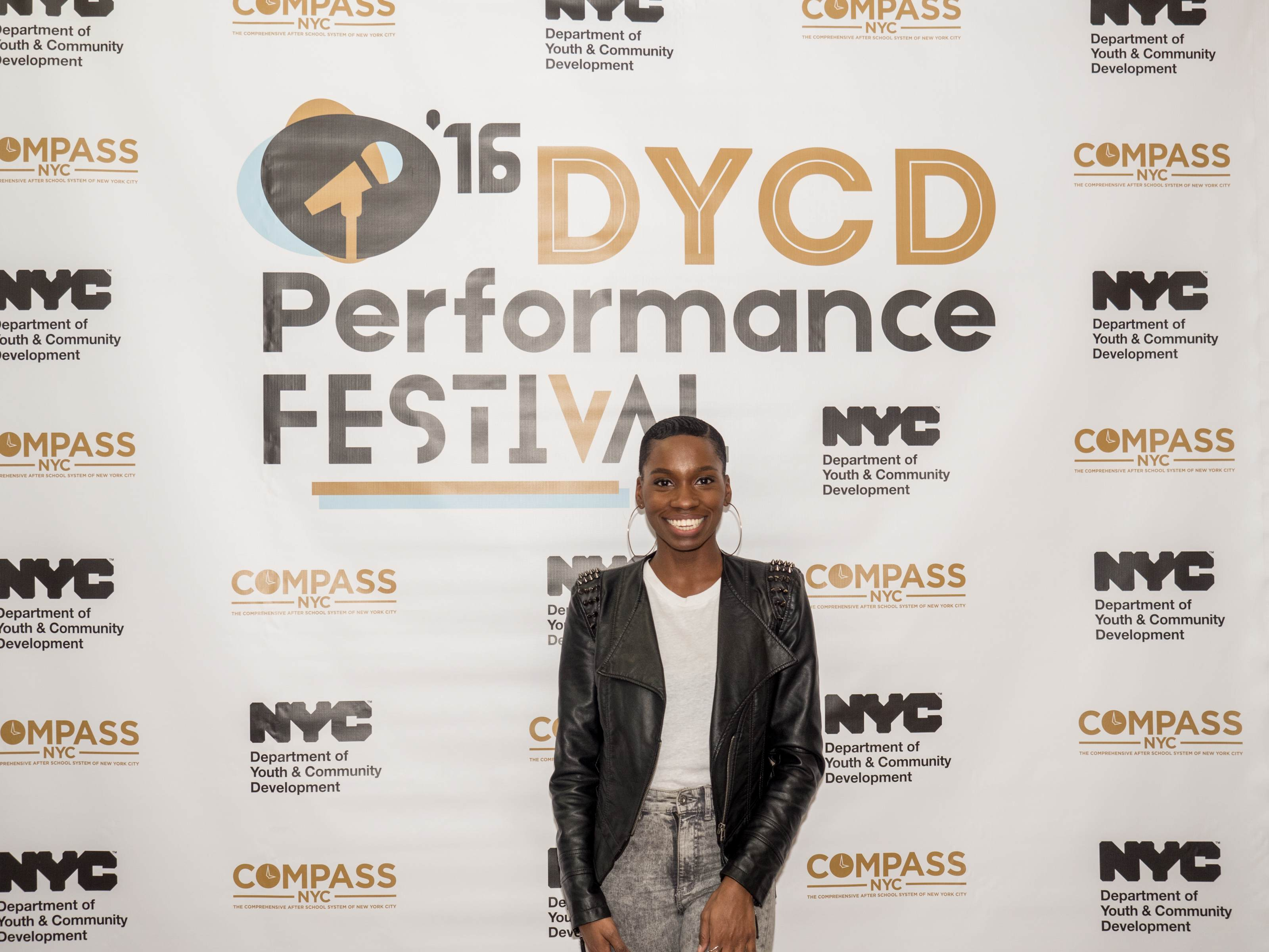 A guest posing in front of a white step and repeat with the DYCD Performance Festival logo large and centered, the DYCD and COMPASS logos repeat in a pattern around the Performance Festival logo.