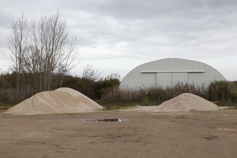 montes de areia com armazem e arvores ao fundo