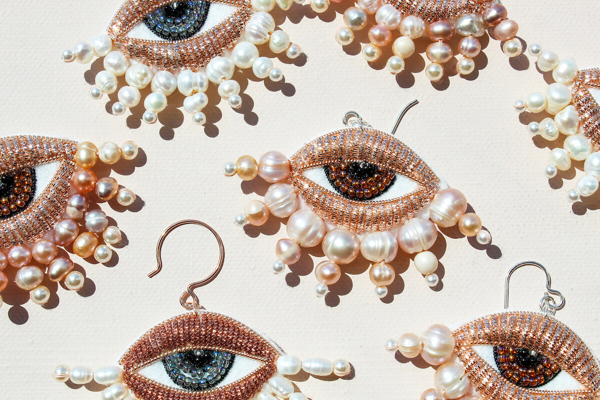 Many earrings lying on a white background, earring are beaded in the shape of eyes