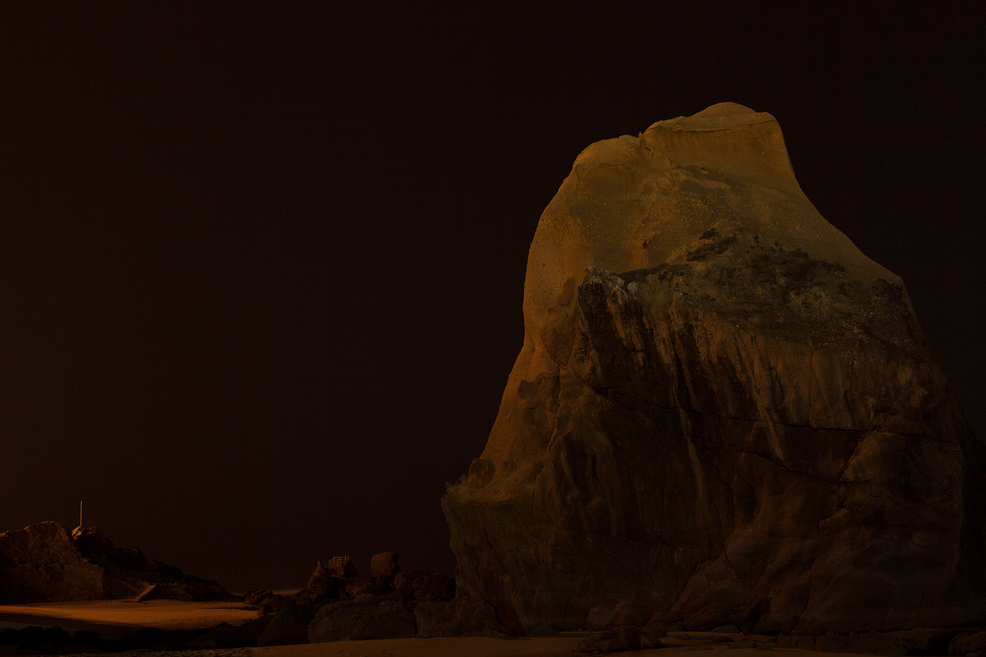 carina martins, vagueamos na noite sem sentido e somos devorados pelo fogo - rocha na praia a noite