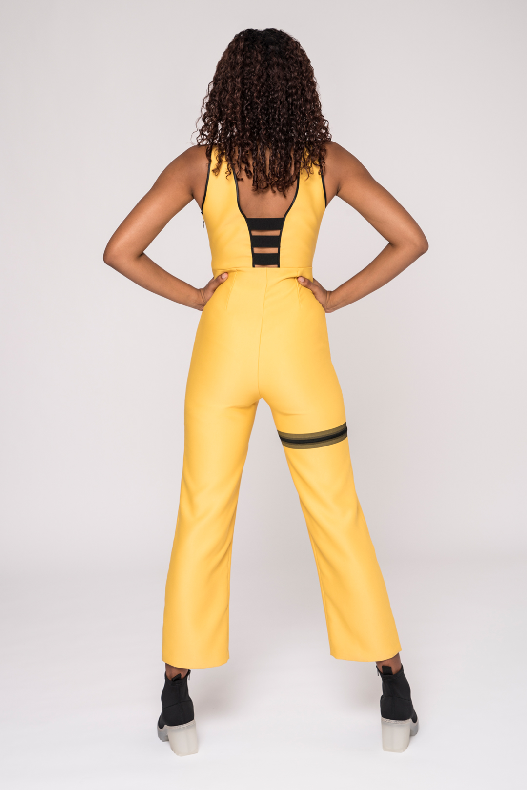 back view of a black model wearing a yellow v-neck jumpsuit