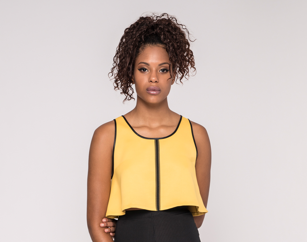 front view of a black model wearing a yellow sleeveless flared top