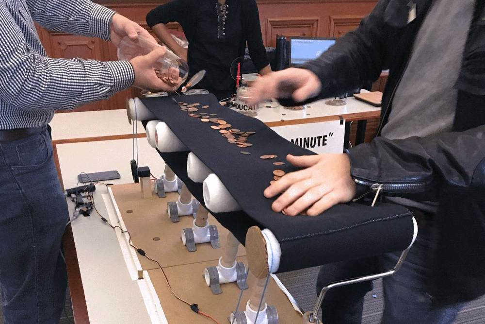 A person empties coins onto a handmade conveyor belt, as another person uses both hands to grab coins