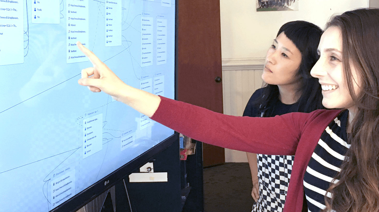 Image link to Auditory Data Design project. Two young women stand looking at a large screen; one is smiling and pointing