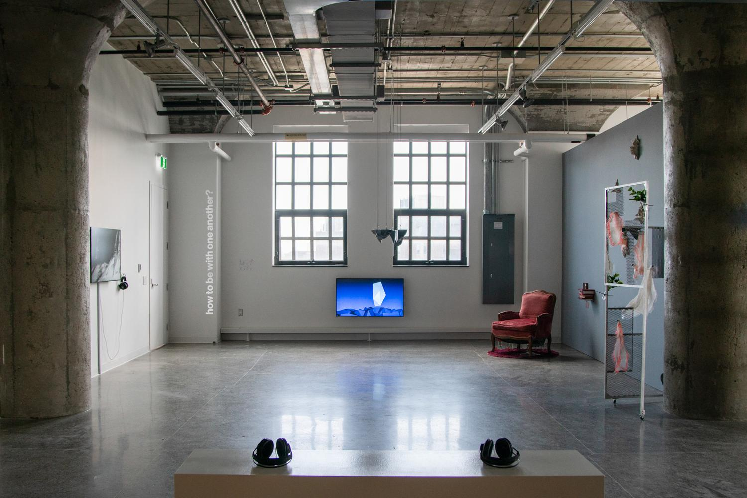 A photo of the south side of the gallery, taken from in the middle of a  gallery. In the foreground, two black headsets rest on a white bench in the centre of the room. An audio piece by Workman. Behind it, various artworks are displayed along the three walls of the gallery. Viewed from left to right in the photo: a TV is hung on eye-level, screening a black-and-white video work by Kolcze. On the white wall, a silvery vinyl text reads, quote, how to be with one another?, end quote. A TV monitor hangs low on the wall of the gallery centred between and below two big windows, screening an animated video by Nuff of a crystal-like landscape. A small black sculpture by Polymetis hangs from the ceiling, in the middle of the room. The wall on the right is dark grey. Against it, a red velvet chair and a stack of zines by Woudenberg. Grey sculptures scattered on the wall by Salazar. A sculptural installation featuring an aluminum door frame, bandages, and plants by Dreifelds.