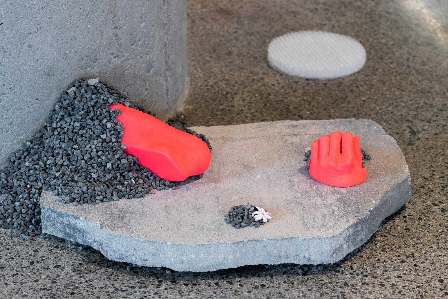 Close-up of neon orange assemblage by Dreifelds, showing partial casts of a hand and a foot in neon resting on a slab of stone and gravel with a jasmine flower. A stack of bubblewrap on the background.