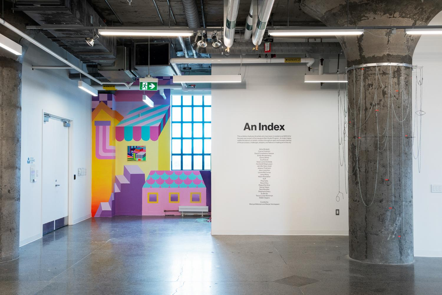 A photo of the start of the exhibition. In the middle of the image, a black vinyl text on a white wall lists the exhibition title and statement, as well as credits the artists and curators. On the left side of the image, a mural by Kim of a colourful dream world that animates a nook in the gallery with a large paned widow. On the right side of the image, a grey structural column is draped with an aluminum chainlinnk site-specific scupture.